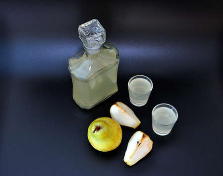 Pear calvados, strong alcohol in two glasses and a glass bottle, ripe fruits nearby on a black background. Close-up. Standard-Bild