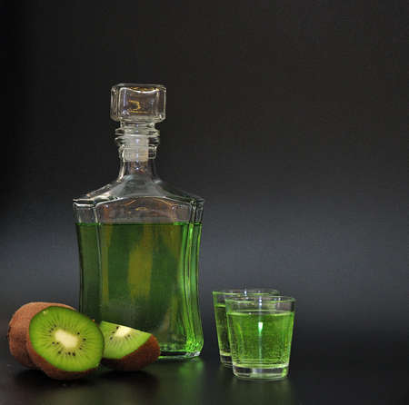 Homemade kiwi-based liqueur in two glasses and a glass bottle, ripe fruits next to it on a black background. Close-up.