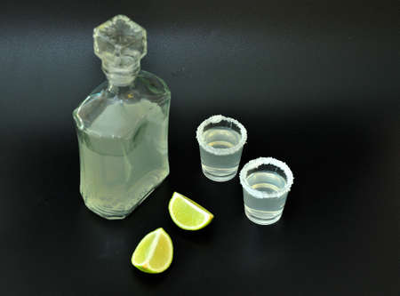 Tequila, a strong homemade alcohol in a glass bottle and two glasses with salt on the edge, next to it are ripe lime pieces on a black background. Close-up. Standard-Bild