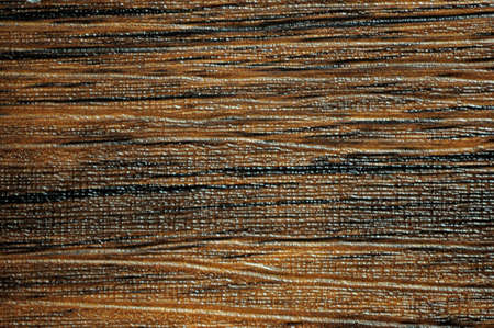 Dark walnut, flat surface of natural brown wood with small light stripes and traces of rough processing. Background, pattern, texture.