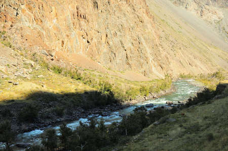 A stormy mountain river rushing along the bottom of a deep canyon, partly in the shade of the setting sun. Valley of the Chulyshman River, Altai, Siberia, Russia. Standard-Bild