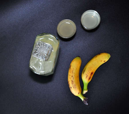 Banana liqueur, glass bottle and two glasses of strong alcohol on a black background, next to two ripe tropical fruits. Close-up.