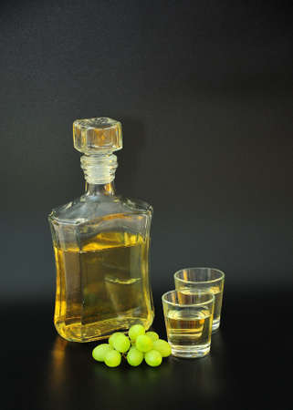 Grappa, a glass bottle and two glasses of strong alcohol on a black background, next to a bunch of ripe white grapes. Close-up. Standard-Bild