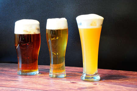 Three different glass goblets with wheat, light and dark beer are on a wooden table. Close-up.