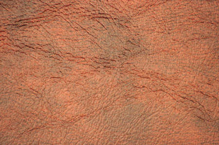 Natural leather of a dark brown color with wrinkles and traces of quality workmanship. Background, pattern, texture.