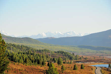 A view of the mountain taiga overgrown with coniferous forest, a fragment of the road and an electric transmission line passing across and snow-capped peaks in the background. Ulagansky District, Altai, Siberia, Russia. Standard-Bild
