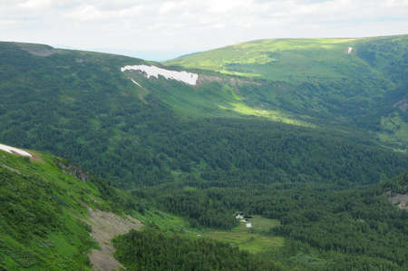 A view of the taiga high in the mountains, with small lakes and remnants of snow. Ivanovskie lakes, Khakassia, Siberia, Russia. Standard-Bild