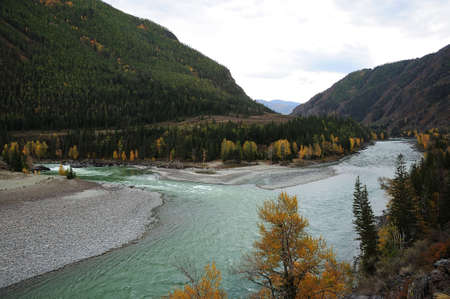 The connection of two mountain rivers at the foot of a high mountain in a picturesque autumn valley. Confluence of the Katun and Argut rivers, Altai, Siberia, Russia. Standard-Bild