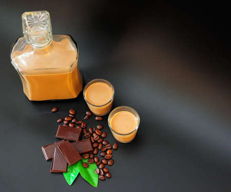 Homemade chocolate-coffee liqueur in a bottle and two glasses on a black background, next to it, roasted coffee beans, mint leaves and chocolate wedges. Close-up.
