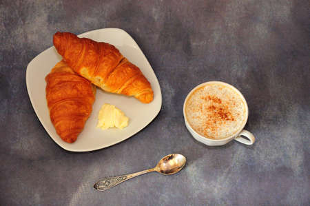 A cup of cappuccino and two fresh croissants with butter on a white ceramic plate. View from above.