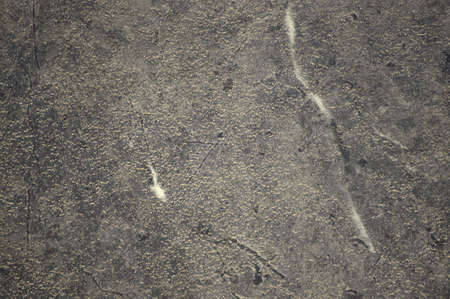 A fragment of dark gray marble with a large white vein running vertically across the surface. Background, pattern, texture.