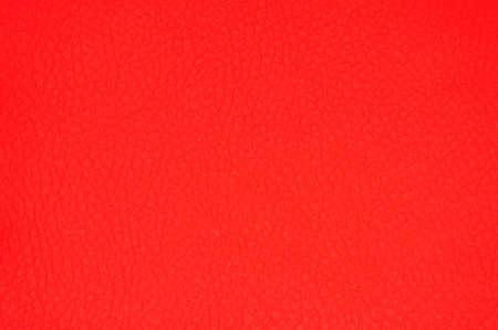 Framgent of genuine leather artificially dyed bright red with vignetting along the edge. Background, pattern, texture.