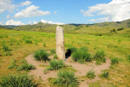 A ritual granite monolith in the center of a picturesque valley surrounded by mountain ranges. Akh-Tas, Khakassia, Siberia, Russia.