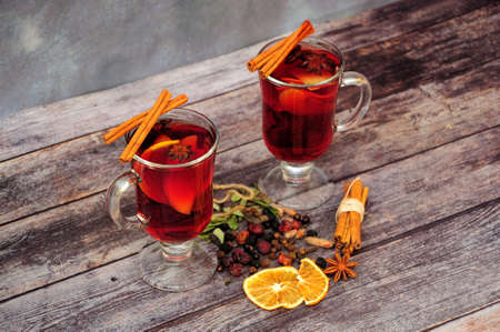 Two glass mugs of hot wine, assortment of spices, orange slices and cinnamon sticks on a wooden table. Close-up.