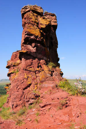 High deep red rock formation at the top of the hill. Mountain range Chests, Khakassia, Siberia, Russia.
