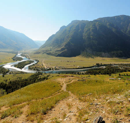 A view from the top of the hill to the picturesque valley bathed in sunlight and the winding river bed below. Chulyshman River, Altai, Siberia, Russia.