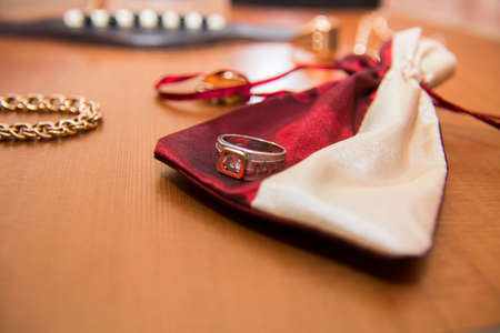 Gold ring, bracelet case and acoustic guitar in the background Stock Photo