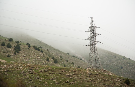 Power lines and electric pylons crossing a lush mountain in Kyrgyzstan Stock Photo