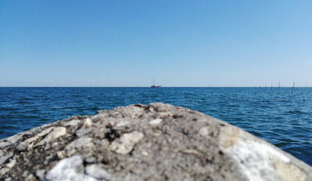 clearly: Landscape of grey stone  with white small shells at the port seaside the blue wave ocean sea with clearly blue sky, the small boat transports in the sea Stock Photo