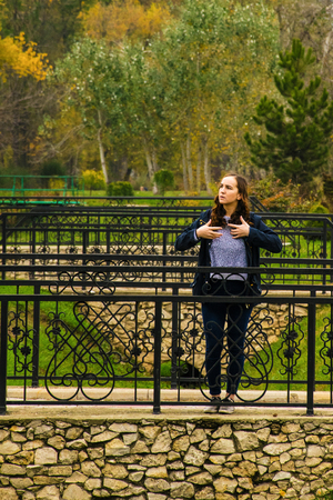 Beautiful woman in blue is standing alone on the stone bridge in the park Stock Photo
