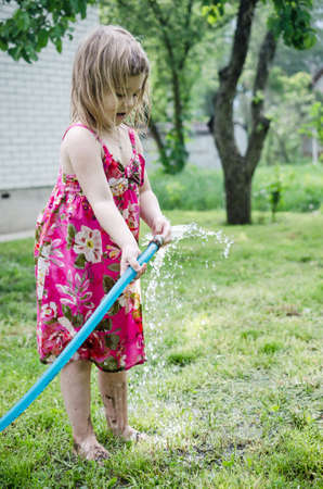 hosepipe: Girl plays with water hose