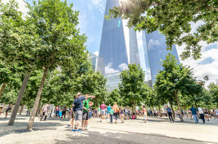 rebuild: NEW YORK - JULY 17: People walk near Freedom Tower (1 WTC) in Manhattan on July 17, 2014. One World Trade Center is the tallest building in the Western Hemisphere. Editorial