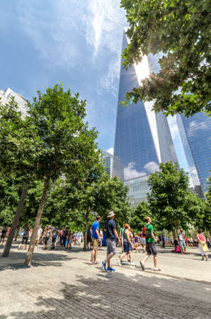 wtc: NEW YORK - JULY 17: People walk near Freedom Tower (1 WTC) in Manhattan on July 17, 2014. One World Trade Center is the tallest building in the Western Hemisphere. Editorial