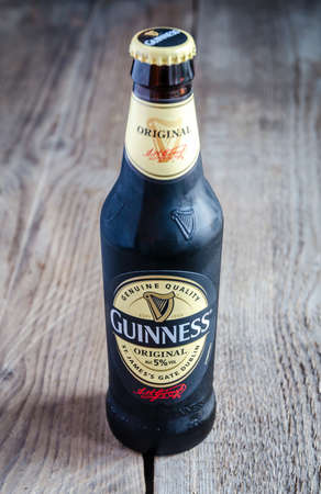guinness beer: SUMY, UKRAINE - OCTOBER 26, 2014: A bottle of Guinness beer on a wooden background. Guinness is one of the most successful beer brands worldwide.