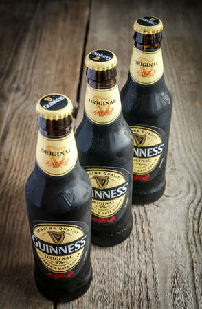 guinness beer: SUMY, UKRAINE - OCTOBER 26, 2014: Three bottles of Guinness beer on a wooden background. Guinness is one of the most successful beer brands worldwide. Editorial