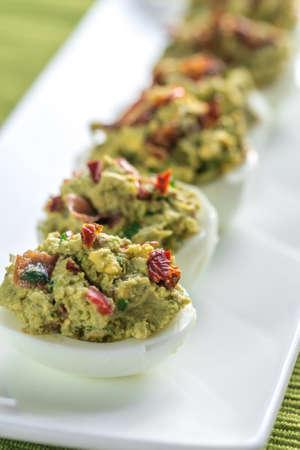 guacamole: Guacamole bacon deviled eggs Stock Photo