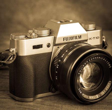 SUMY, UKRAINE - SEPTEMBER 7, 2016: Fujifilm X-T10 Mirrorless Digital Camera on vintage background. Old fashioned photo.