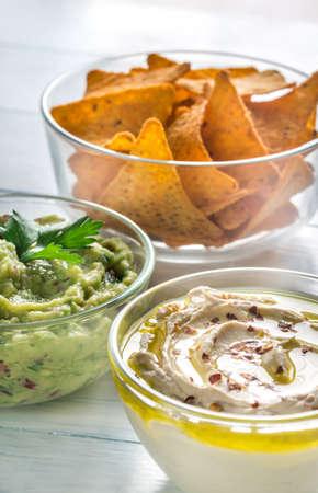 Bowls of hummus and guacamole with tortilla chips Stock Photo