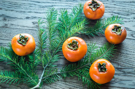 Fresh persimmons with fir branch on the wooden background