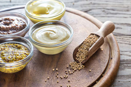 sweet mustard: Different kinds of mustard on the wooden background