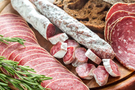 Different kinds of salami with dark-rye bread Stock Photo