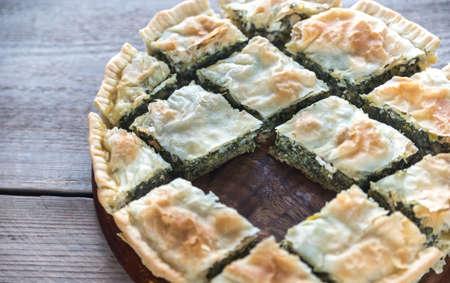 Spanakopita - Greek spinach pie on the wooden board Stock Photo