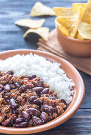 Bowl of chili con carne with white rice and tortilla chips