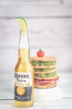 SUMY, UKRAINE - APRIL 05, 2017: Bottle of Corona Extra Beer with crispbread sandwich. Corona is one of the top-selling beers worldwide.