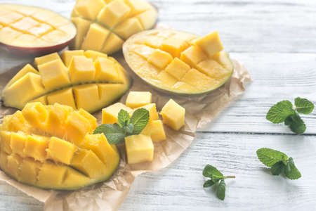 Halves of mango on the wooden background