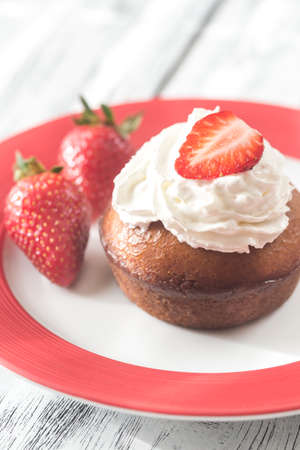 Rum baba decorated with whipped cream and fresh strawberries