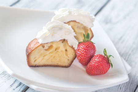 Rum baba decorated with whipped cream on the plate