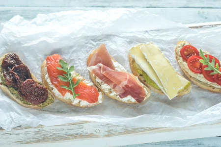 hams: Crostini with different toppings on the wooden background Foto de archivo