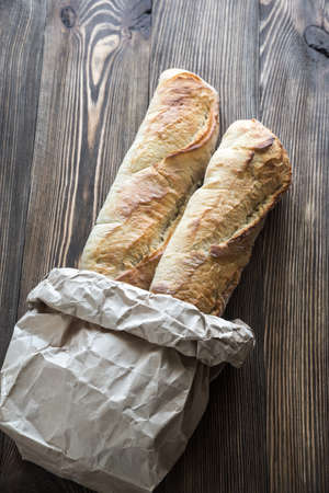 Two baguettes on the wooden background Stock Photo