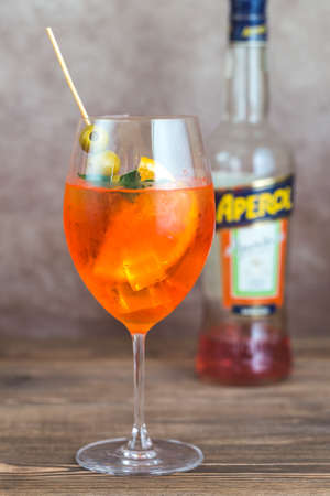 SUMY, UKRAINE- JULY 27, 2017: Glass of Aperol Spritz cocktail with bottle of Aperol on the wooden background. Aperol is famous Italian aperitif.