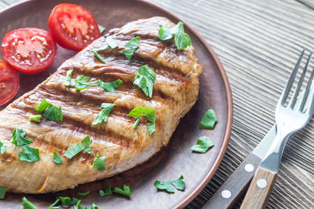 Grilled turkey breast with fresh parsley and cherry tomatoes Standard-Bild