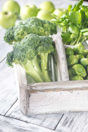 Green vegetables with herbs in the wooden basket Stock Photo