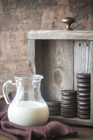 Chocolate cookies with creamy filling and milk in a jag