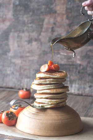 Pancakes with fresh persimmon and maple syrup