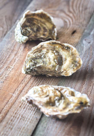 Raw oysters on the wooden background Stock Photo