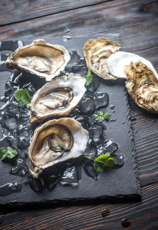 Raw oysters on the black stone board